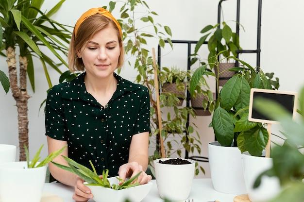 Giardinaggio della donna del colpo medio al chiuso