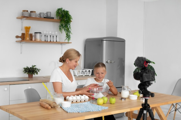 Medium shot woman and girl cooking together