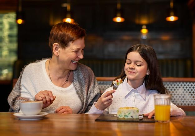 Medium shot woman and girl at table