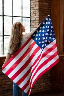 Среднего выстрела женщина держит американский флаг