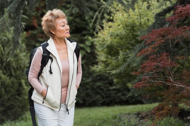 バックパックを保持しているミディアムショットの女性