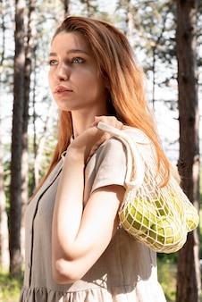 ミディアムショットの女性がバッグを持っています