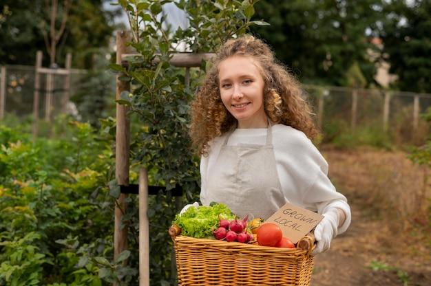 Donna con colpo medio che tiene cesto con verdure