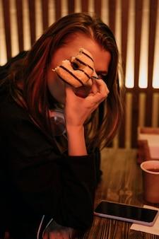 Medium shot woman holding bitten donut