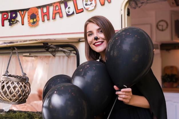Среднего выстрела женщина держит черные воздушные шары