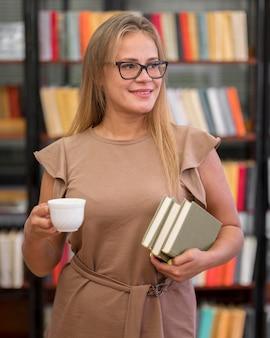 本を保持しているミディアムショットの女性