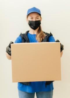 Средний выстрел женщина, держащая коробку