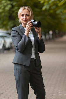 Medium shot woman holding camera