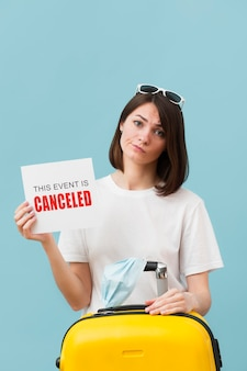 Medium shot woman holding a card with a canceled event message