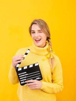 Medium shot woman holding clapboard