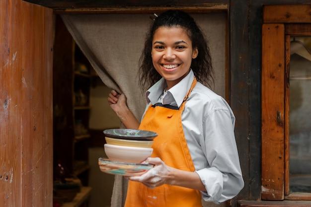 Donna del colpo medio che tiene i vasi di terracotta