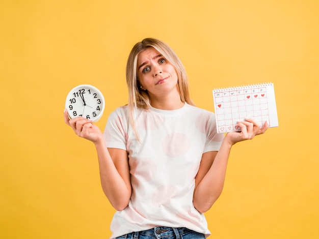 Medium shot of woman holding clock and period calendar