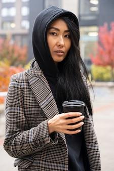 コーヒーカップを保持しているミディアムショットの女性