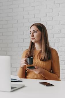 Tazza di caffè della holding della donna del colpo medio