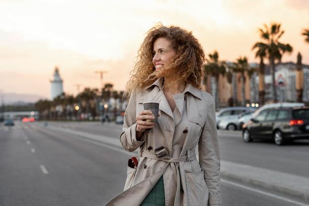 Donna del colpo medio che tiene tazza di caffè