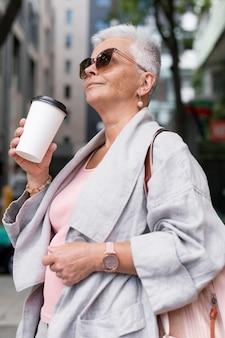 Donna del colpo medio che tiene la tazza di caffè