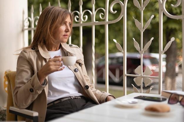Medium shot woman holding coffee cup