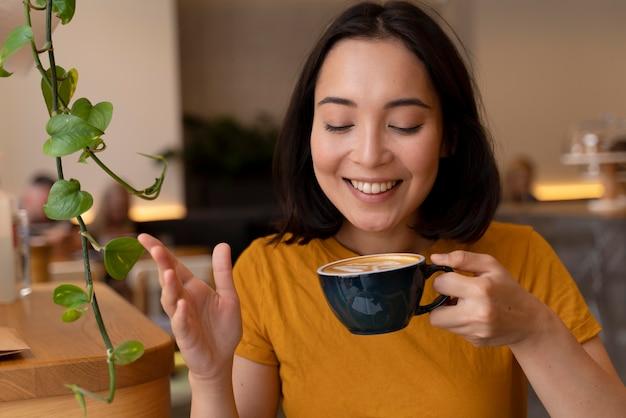 Medium shot womanholding coffee cup