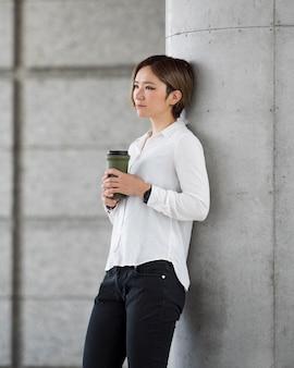Donna del colpo medio che tiene la boccetta del caffè?