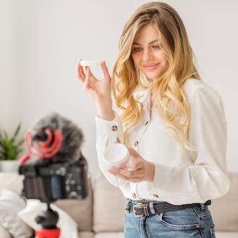 Medium shot woman holding cream container