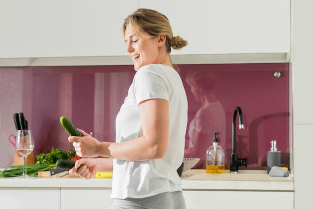Medium shot woman holding a cucumber in the kitchen