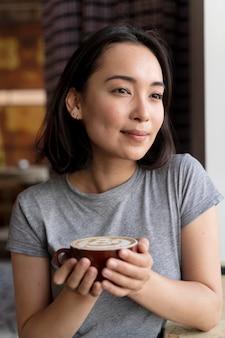 Medium shot woman holding cup