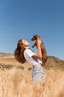 Donna del tiro medio che tiene cane carino