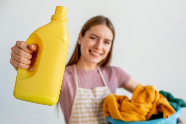 Среднего выстрела женщина, держащая моющее средство