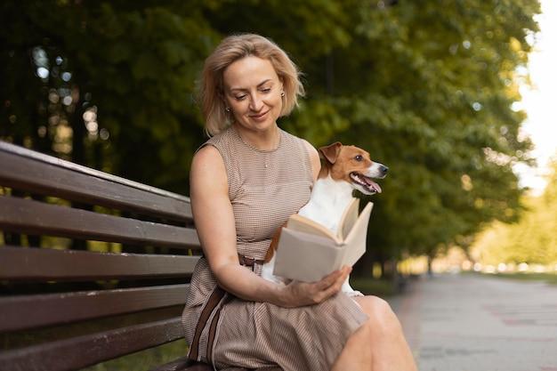 公園で犬を保持しているミディアムショットの女性