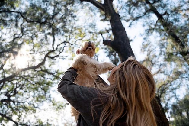 犬を持ち上げるミディアムショットの女性