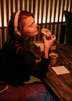 Medium shot woman holding donut