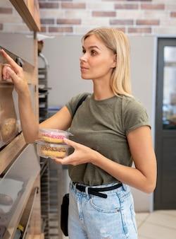 ドーナツを持っているミディアムショットの女性