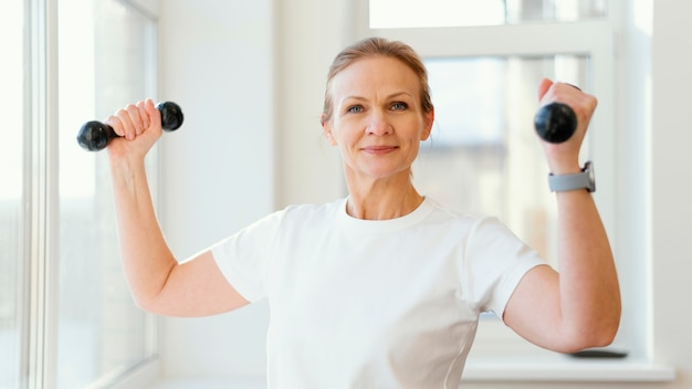 Medium shot woman holding dumbbells