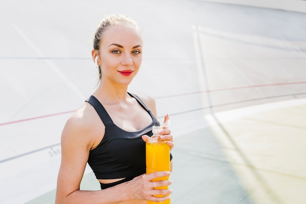 Medium shot of woman holding energy drink