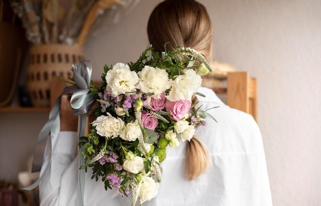 Средний снимок женщины, держащей букет цветов