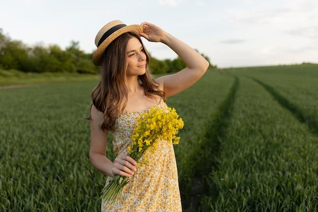 Donna con colpo medio che tiene i fiori