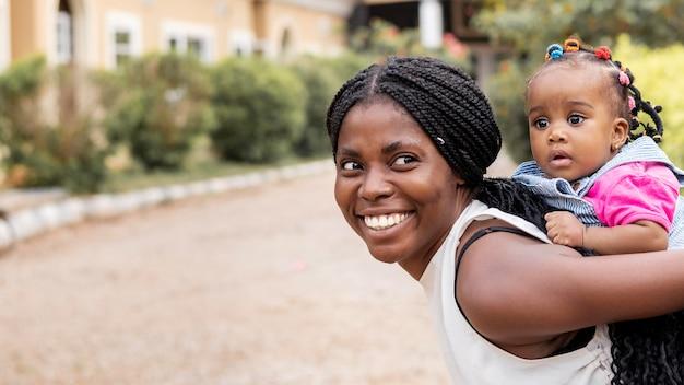 Medium shot woman holding girl
