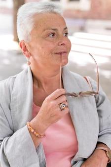 Donna con colpo medio che tiene gli occhiali