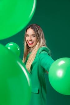 Donna del colpo medio che tiene i palloni verdi