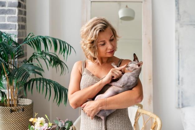 Среднего выстрела женщина, держащая лысую кошку