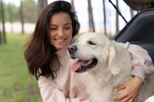 Donna del colpo medio che tiene cane felice