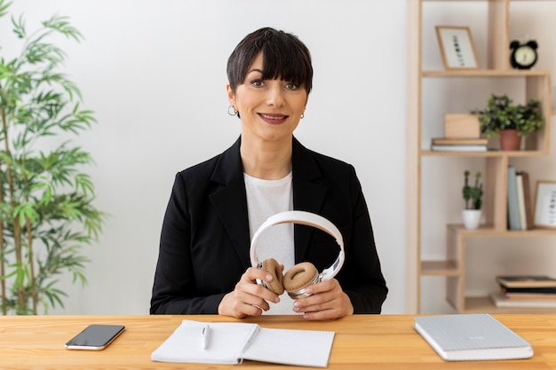 Medium shot woman holding headphones