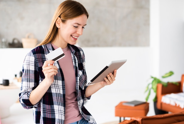 Medium shot of woman holding her credit card and looking at the tablet