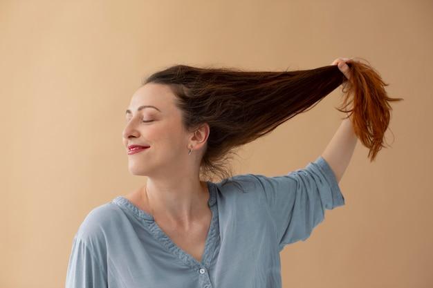 Среднего выстрела женщина держит ее за волосы