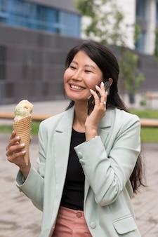 アイスクリームを保持しているミディアムショットの女性