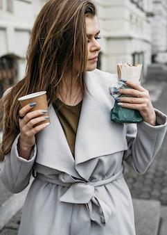 Medium shot woman holding kebab and coffee