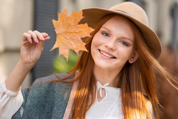葉を保持しているミディアムショットの女性
