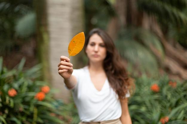 Средний выстрел женщина, держащая лист