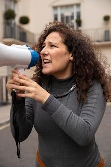 Medium shot woman holding megaphone