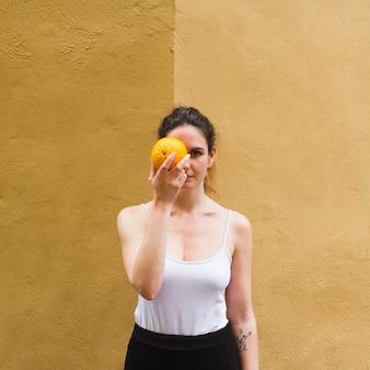 Medium shot woman holding an orange covering her eye